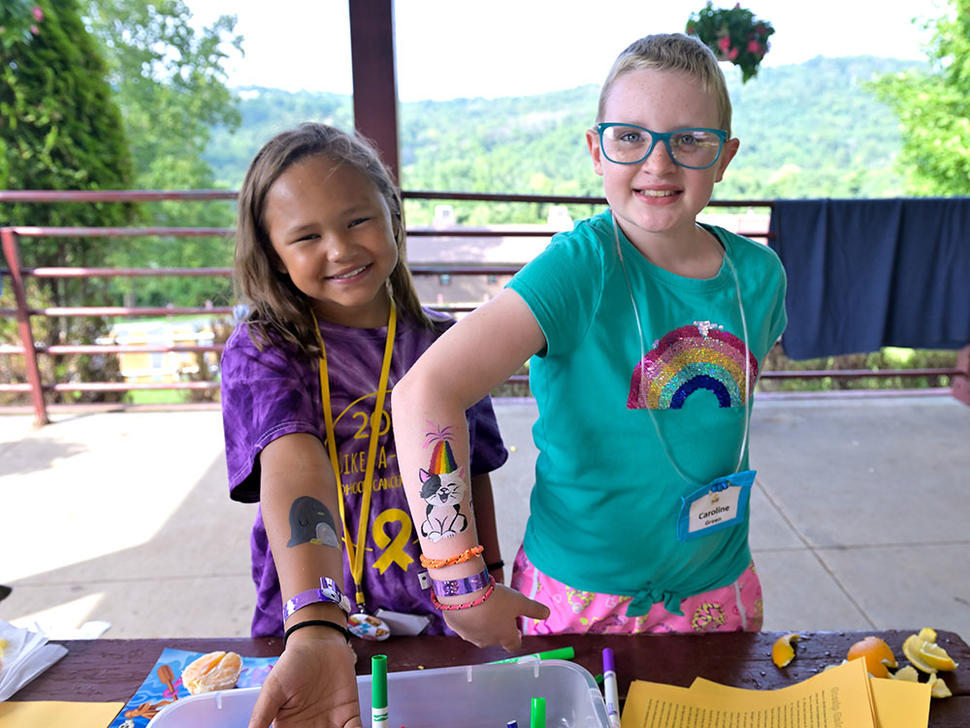 Campers show off their painted designs on their arms at Camp Fantastic.