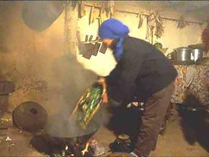 woman cooking in a wok with a lot of smoke